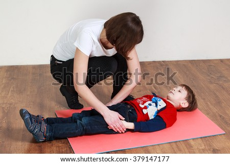 Physiotherapy for children. Little boy is lying on the mat at a gym, trainer is helping him to do an exercise - stock photo