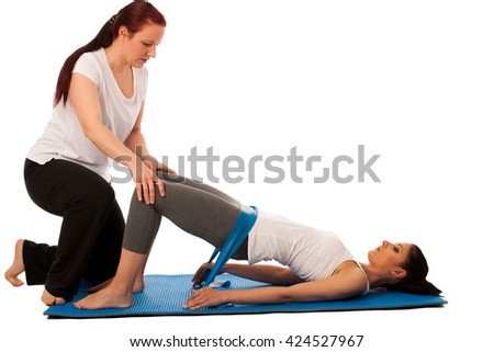 Physiotherapy - therapist doing   exercises with band for improving back strenght and stability with a patient to recover  after injury isolated - stock photo