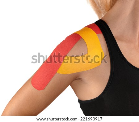 Physiotherapy treatment with therapeutic tape for shoulder pain, aches and tension. It is also used for prevention and treatment in competitive sports. - stock photo
