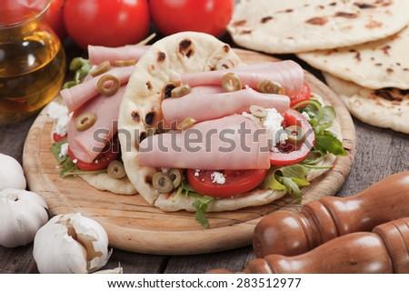 Piadina romagnola, italian flatbread sandwich with rocket salad, ricotta cheese and baloney - stock photo