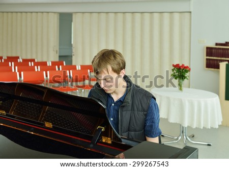 Pianist plays on black grand piano in empty room - stock photo