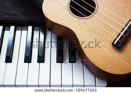 Piano key and ukulele - stock photo