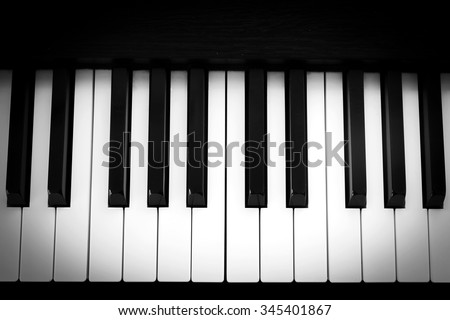 Piano keyboard. Black and white theme. Top view. With dark vignette. - stock photo