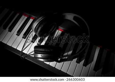 Piano keyboard with headphones - stock photo