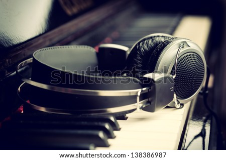 Piano keyboard with headphones for music - stock photo