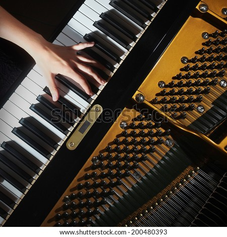 Piano Music instrument grand piano keys with hands. Pianist playing piano keyboard - stock photo