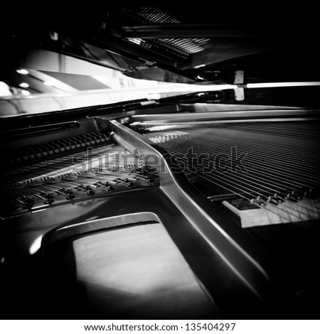 Piano strings and hammer detail black and white - stock photo