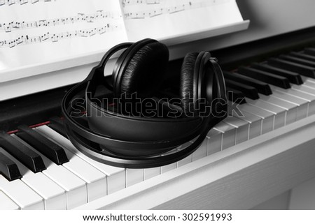 Piano with headphones and music notes close up - stock photo