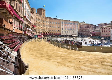 Piazza del Campo in the preparation of the sandy substrate for the place of the Palio horse race, with the Public Palace, Siena, Tuscany, Italy - stock photo