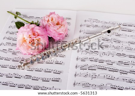 Piccolo on sheet music with pink roses isolated - stock photo