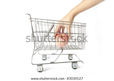 pick apple, female hand pick or put apple into silver supermarket trolley. - stock photo