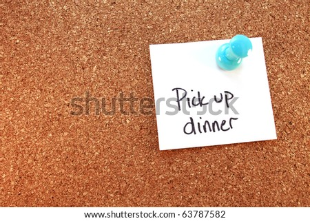 Pick Up Dinner A pick up dinner note tacked on corkboard. Horizontal. - stock photo