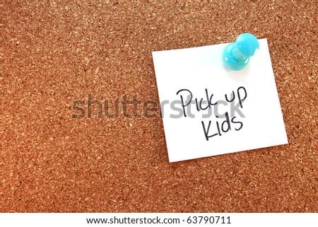 Pick Up Kids A pick up kids note tacked on corkboard. Horizontal. - stock photo