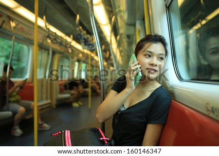 pick up the phone call go to the destination, talk on smart phone with good news, beautiful lady watch outside, in railroad box car MTR, hong kong,china, asia - stock photo