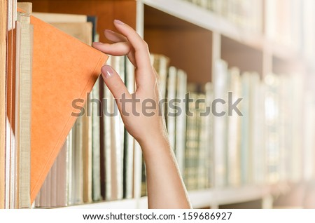 Picking a book - stock photo