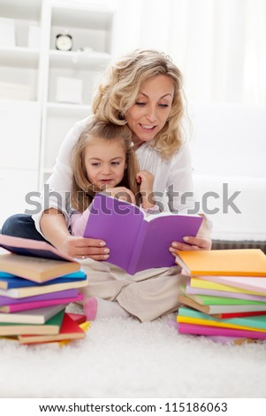 Picking a story to read - little girl and her mother at home - stock photo