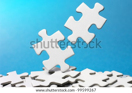 Picking out two fitting puzzle pieces.(horizontal) - stock photo