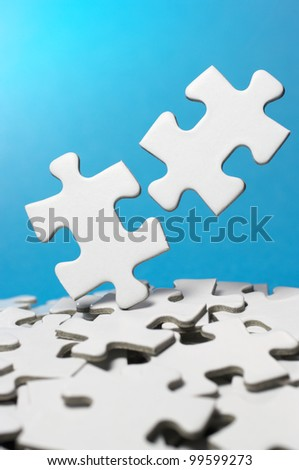 Picking out two fitting puzzle pieces.(vertical) - stock photo