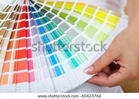 Picking the right paint - woman hand with color sample chart - stock photo