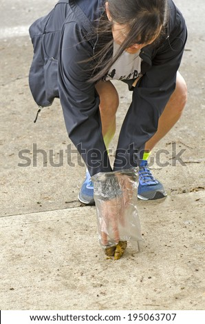 Picking up dog poop off of the concrete sidewalk in a city setting - stock photo
