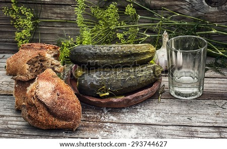 Pickled cucumbers with dill and vodka shot glass on wooden background in country style.Photo tinted.Selective focus - stock photo