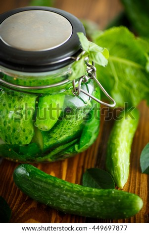 pickled cucumbers with spices in glass jar - stock photo