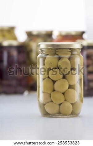 Pickled Green Olives Jar with Other Pickles Jars in Background - stock photo