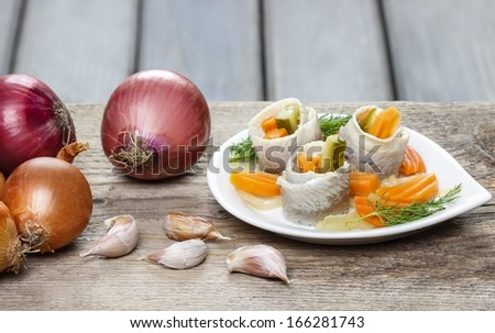 Pickled herring rolls with vegetables on brown wooden background. Fresh onions and garlic, copy space. - stock photo
