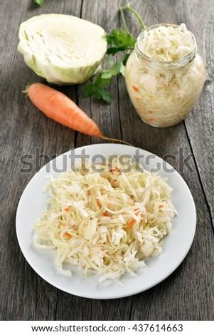 Pickled marinated cabbage (sauerkraut) on wooden background - stock photo