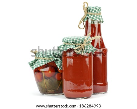 Pickled tomatoes and tomato sauce, ketchup in glass jar on a white background  - stock photo