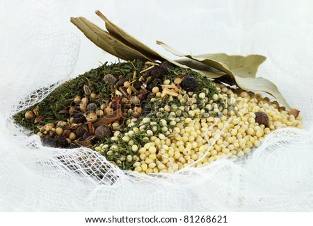 Pickling spices lying in a loose piece of cheesecloth ready to be used to make pickles. - stock photo
