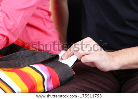 Pickpocket are stealing mobile phone from bag, close up - stock photo