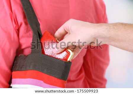 Pickpocket are stealing wallet from bag, close up, on light background - stock photo