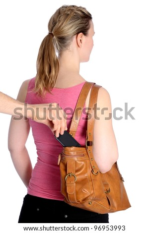 Pickpocketing of a mobile phone out of a handbag - stock photo