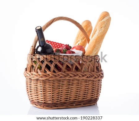 Picnic basket full of food and drinks on white background - stock photo
