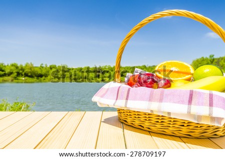 Picnic basket full of fresh fruits on wooden table - stock photo