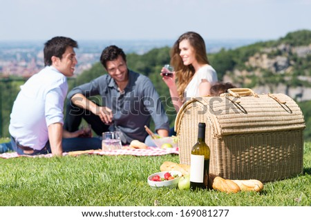 Picnic Basket In Front Of Group Of Friend Enjoying Wine Outdoor - stock photo
