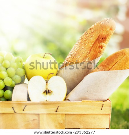 Picnic Basket with Fresh Food, Bread, Apples, Fruit on Nature Background. Wiith sunshine effects - stock photo