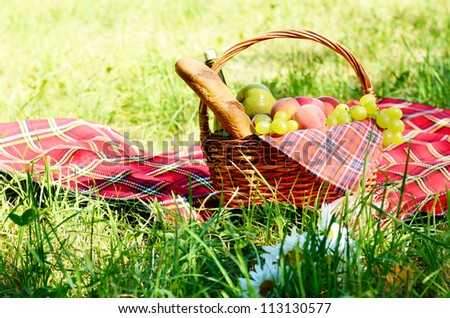 Picnic basket with red napkin fool of fruits, bread and wine - stock photo
