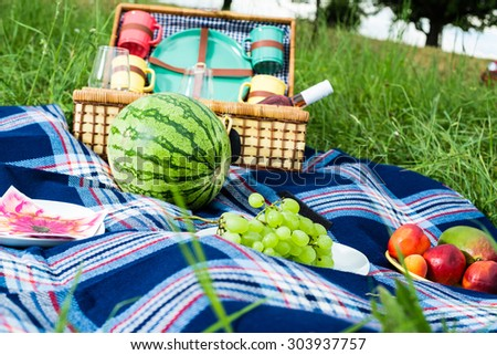 Picnic blanket and basket with fruits and wine bottle in a sunlit grassy meadow - stock photo
