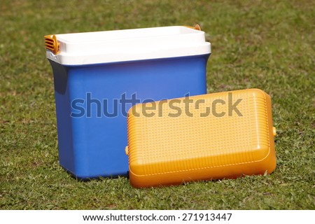 Picnic cooler in the grass in blue and orange tone. Horizontal - stock photo