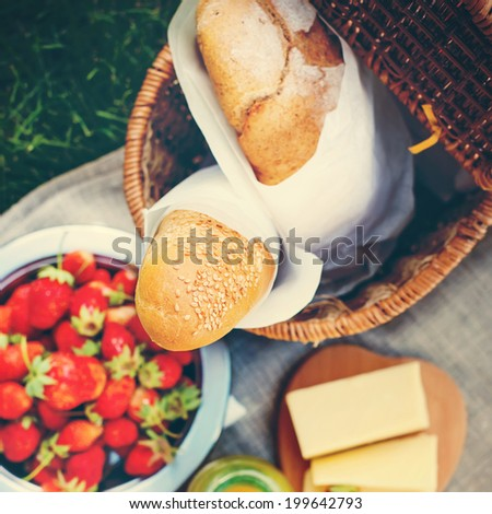 Picnic Food. Fresh Bread, Strawberry, cheese and  honey on a sacking cloth, selective focus, toned  - stock photo