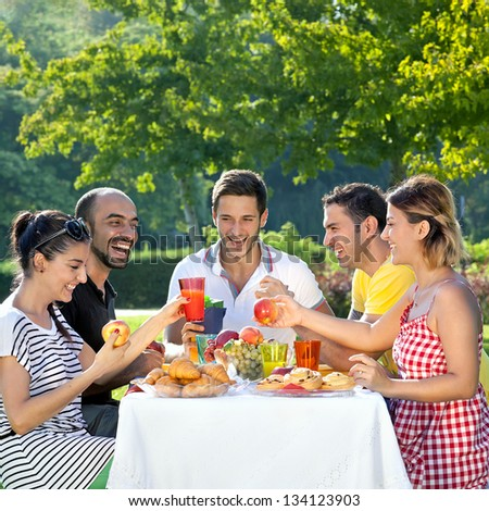Picnic. Multi ethnic friends sharing an enjoyable meal seated at a table outdoors in the garden laughing and joking together - stock photo