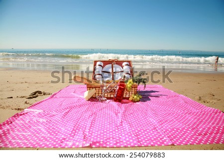 Picnic on the beach. A typical Laguna Beach California picnic with the Pacific Oceans Gentle Tide rolling in slowly as the warm February Sun Rolls across the beautiful blue sky.  - stock photo