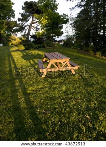 Picnic table at sunset with a long shadow. Long shadow of human legs. Oakville, Ontario, Canada. - stock photo