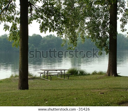 picnic table at the river - stock photo