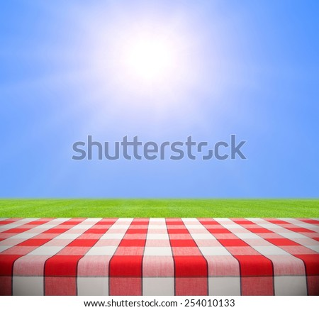 Picnic table in grass field against clear blue sky with sun - stock photo
