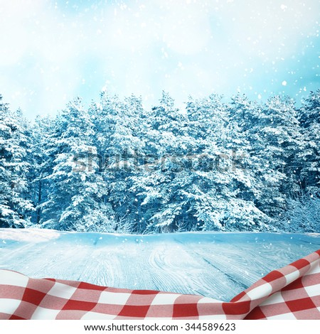Picnic table in winter forest with red tablecloth with space for your object - stock photo