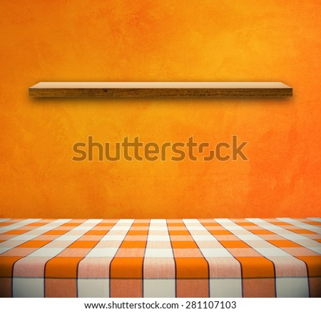 Picnic table on orange wall with shelf - stock photo