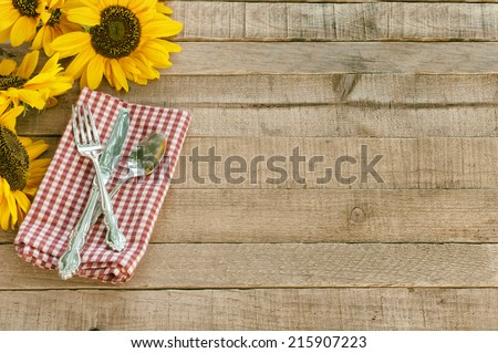 Picnic Table Setting with Pretty Cheerful Sunflowers, Silverware, red  white checked napkin, brown Rustic Wood Board Background, empty room or space for copy, text, your words.  Horizontal  - stock photo